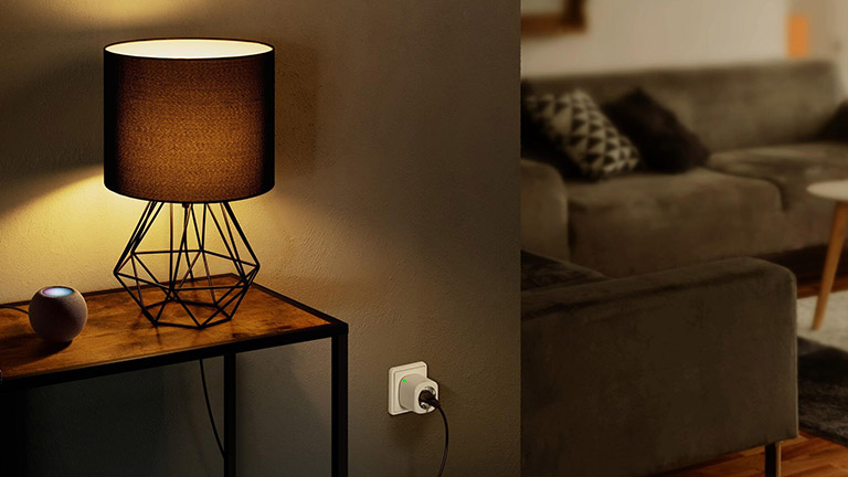 Ein Apple HomePod Mini auf einem Tisch. Daneben steht eine Lampe, die über eine Eve Energy mit dem Strom verbunden ist.