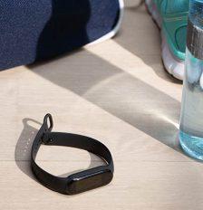 Das Fitness-Armband Mi Smart Band 5 von Xiaomi liegt auf einem hellen Holztisch. Ringsherum befinden sich Sportutensilien.