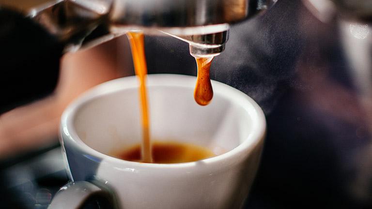Langsam läuft Espresso von einer Kaffeemaschine in eine kleine Espresso-Tasse.