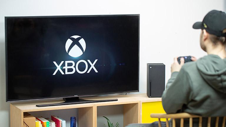 Eine Person sitzt vor einer Xbox Series X. Auf dem Fernseher ist der Startbildschirm zu sehen.