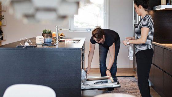 Eine Person bückt sich über einen geöffneten Geschirrspüler.