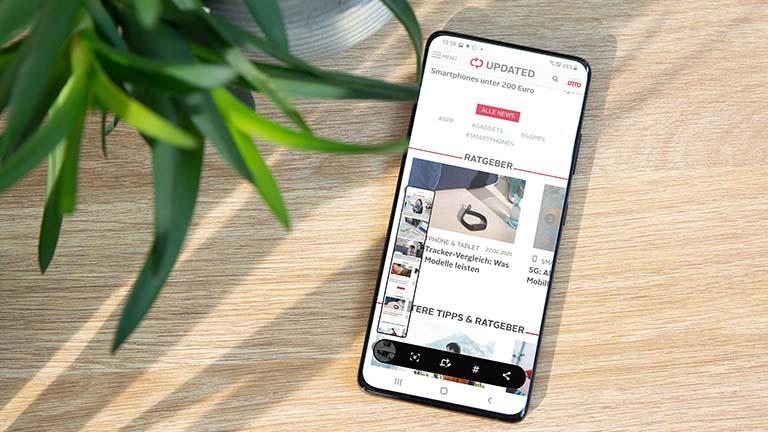 Ein Samsung Galaxy S21 Ultra 5G liegt auf einem Tisch. Auf dem Bildschirm ist zu sehen, wie ein Scroll-Screenshot aufgenommen wurde.