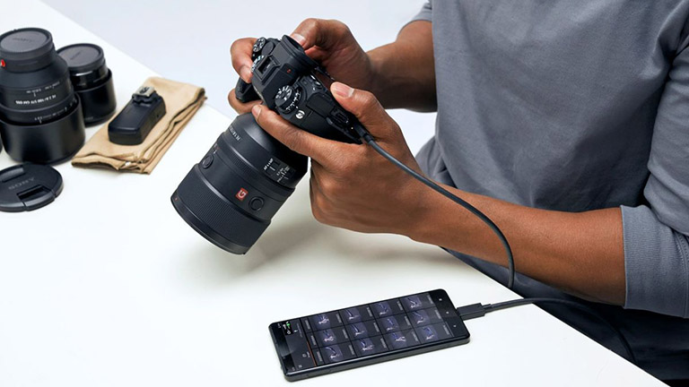 Eine Person hält die Sony Alpha 1, die gerade Bilder per Kabel an ein Smartphone überträgt.