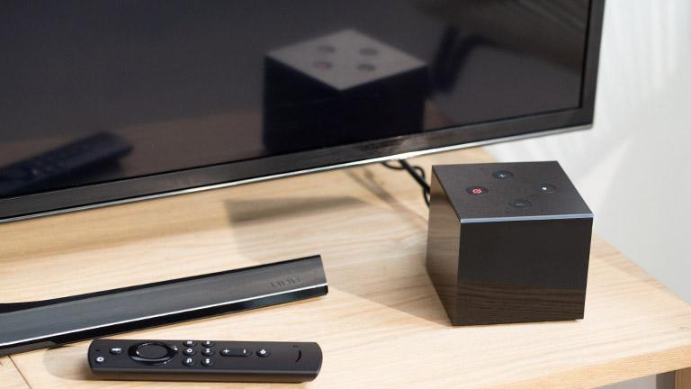 Der Amazon Fire TV Cube steht vor einem Fernseher. Daneben ist die Fernbedienung zu sehen.