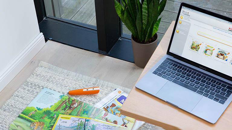Ein Tiptoi-Stift und Bücher liegen auf dem Boden, auf einem Tisch daneben steht ein Laptop, auf dem der Tiptoi-Manager geöffnet ist.