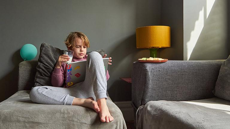 Ein Junge sitzt entspannt mit einem Glas Milch und einem Tablet auf einem Sessel.