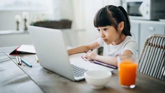 Ein junges Mädchen sitzt an einem Küchentisch vor einem aufgeklappten Laptop. Neben ihr befinden sich ein paar Stifte und ein volles Glas Saft.