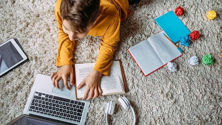 Ein Kind liegt vor einem Notebook. Neben ihm sind Hefte und Zettel zu sehen.
