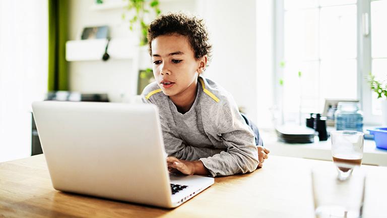 Ein Kind sitzt an einem Tisch und bedient ein Notebook.
