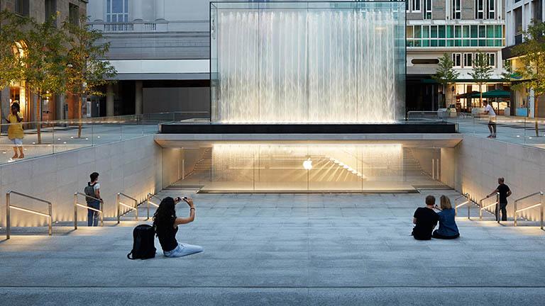 Mehrere Personen sitzen auf einer Treppe und schauen auf den künstlichen Wasserfall vor einem Apple Store in Italien.