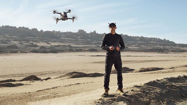 Ein Mann steht in sandiger Umgebung. Er hält einen Drohnencontroller in der Hand und trägt die FPV-Brille von DJI. Vor ihm fliegt die DJI FPV.