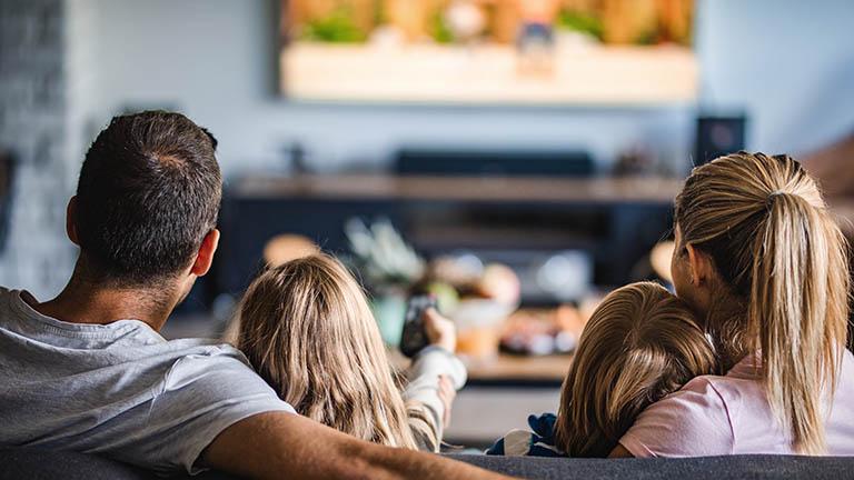 Eine Familie mit zwei Kindern sitzt vor dem Fernseher und schaut sich einen Film an.
