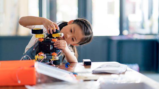 Ein Kind bastelt an einem elektronischen Spielzeug zum Selberbauen.