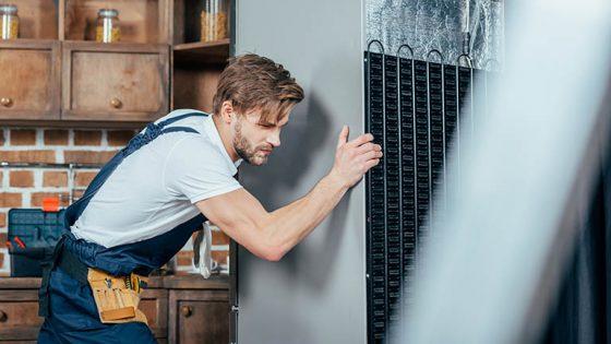 Eine Person verschiebt einen Kühlschrank in einer Küche.