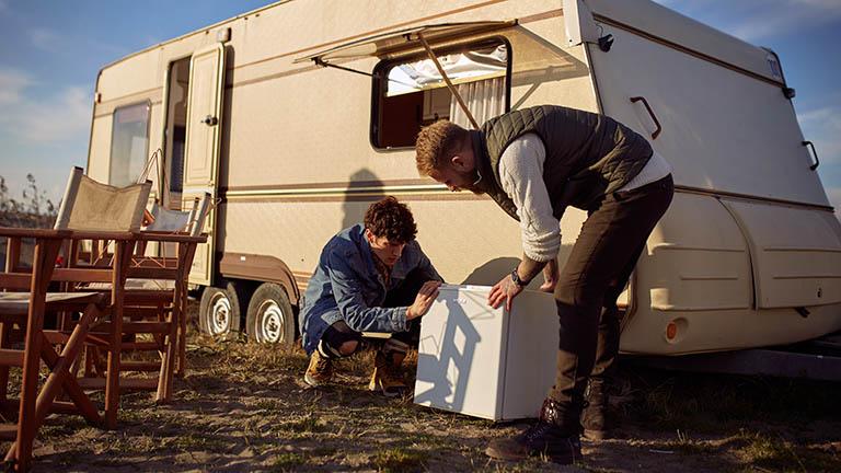 Zwei Personen beugen sich über einen Kühlschrank vor einem Wohnwagen.