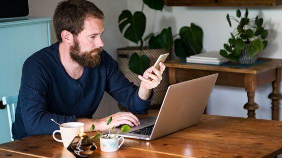 Eine Person sitzt an einem Tisch vor dem Laptop und macht etwas auf ihrem Smartphone.