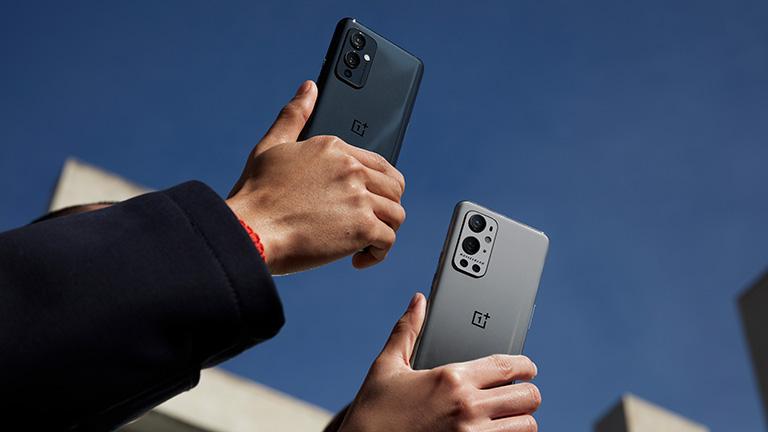 Zwei Hände halten das OnePlus 9 und das 9 Pro in die Luft. Zu sehen sind die Rückseiten der Smartphones.