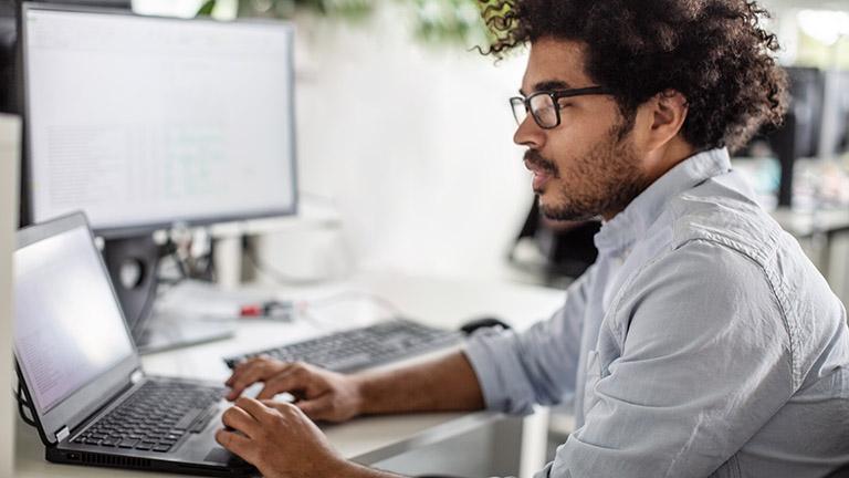 Eine Person sitzt vor einem Notebook und arbeitet.