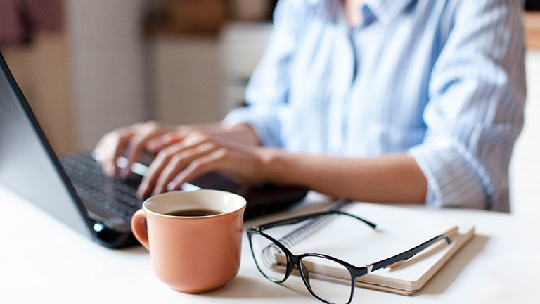 Eine Person sitzt vor einem Notebook und arbeitet. Neben ihr steht eine Tasse Kaffee.