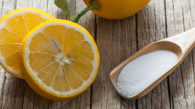 Eine aufgeschnittene Zitrone neben der ein Löffel mit Zitronensäure in Pulverform liegt.