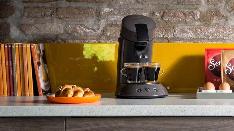 Die Philips Senseo Original auf einer Küchenzeile. Daneben steht ein Teller mit Gebäck.
