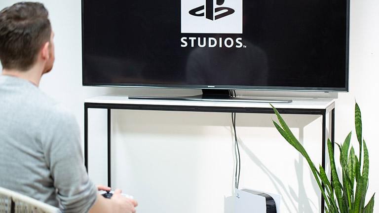 Eine Person sitzt vor einem Fernseher. Darunter steht eine PlayStation 5.