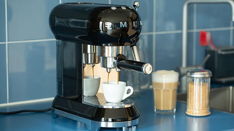 Eine Espressomaschine im Retro-Look der Marke Smeg steht auf einer Küchenzeile und bereitet einen Espresso zu.