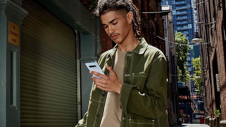 Eine Person hält ein Samsung Galaxy S10 in der Hand, während sie draußen unterwegs ist.