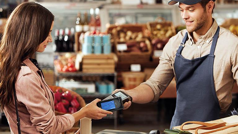 Eine Person bezahlt in einem Lebensmittelgeschäft mit dem Smartphone.