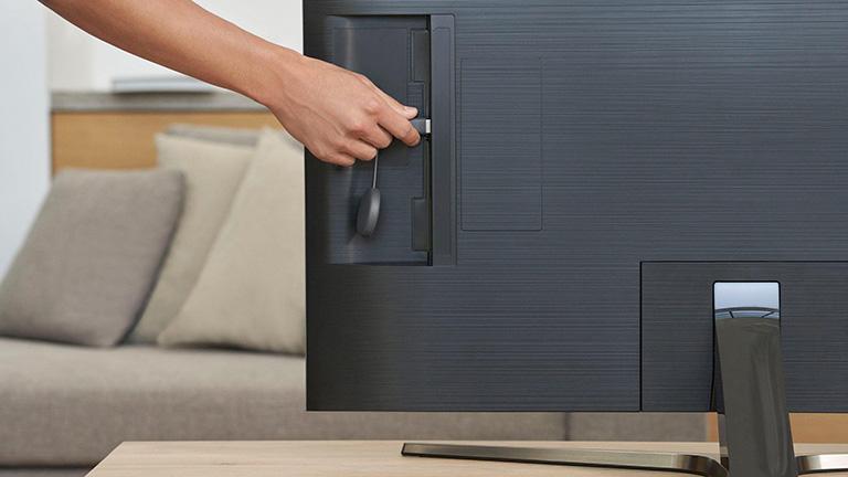 Eine Person steckt ein Google Chromecast in einen HDMI-Anschluss hinterhalb des Fernsehers.