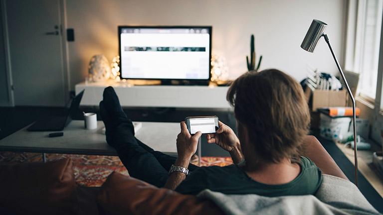 Eine Person sitzt auf einem Sofa und hält ihr Smartphone in der Hand. Auf dem Fernseher ist ein gespiegeltes Bild vom Handy-Display zu sehen.