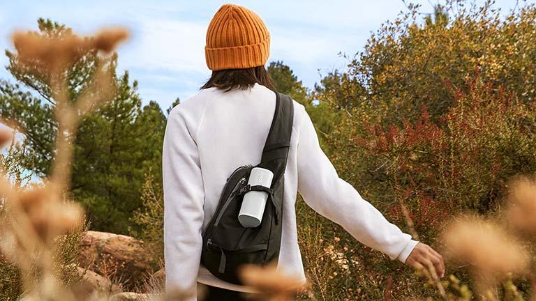 Ein Mann streift durch ein Feld. An seinem Rucksack hängt der Bluetooth-Lautsprecher Sonos Roam in weiß.