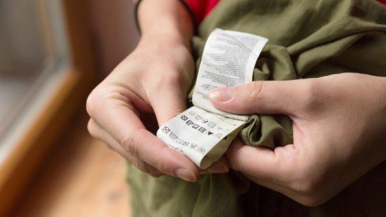 Eine Person schaut auf den eingenähten Zettel mit den Pflegehinweisen.