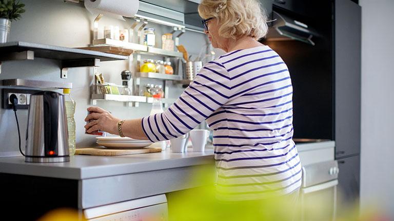 Eine Person steht in der Küche, auf der Arbeitsplatte steht ein eingeschalteter Wasserkocher.