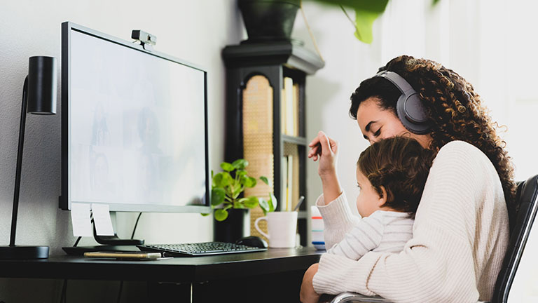 Eine Person sitzt mit einem Kind auf dem Schoß in einer Video-Besprechung.