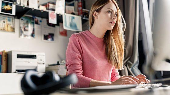 Eine Frau sitzt tippend an einem PC.