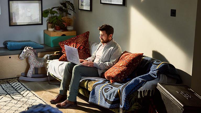 Ein Mann sitzt auf einem Sofa, auf seinen Knien balanciert er ein aufgeklapptes Notebook, seine Hände ruhen auf der Tastatur.
