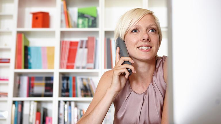 Eine Person sitzt an einem Schreibtisch und telefoniert mit einem Festnetztelefon.