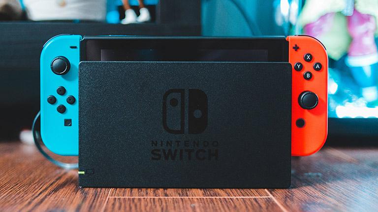 Die Nintendo Switch steht im TV-Dock auf einem Holztisch. Gut zu erkennen sind der rote und der blaue Joy-Con-Controller.