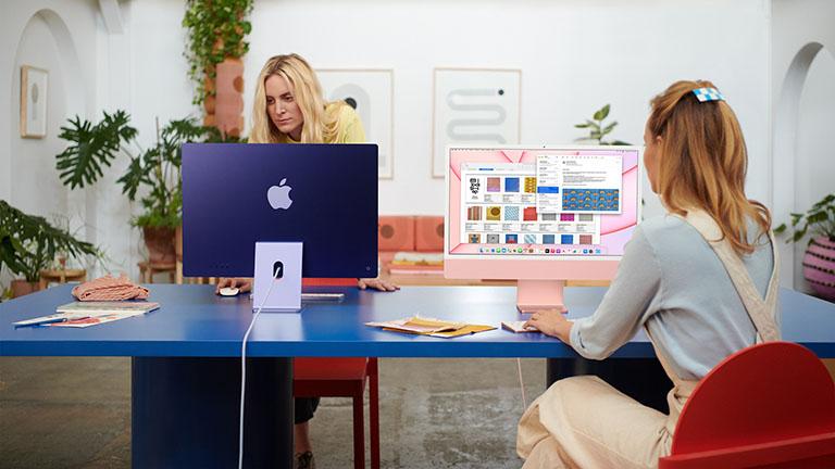 Zwei Personen arbeiten jeweils an einem neuen iMac in 24 Zoll. Einer der iMacs ist Violett, der andere Rosé.