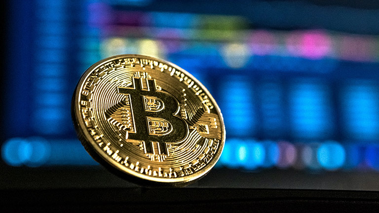 Aufnahme einer Goldmünze mit dem Bitcoin-Logo, im unscharfen Hintergrund befindet sich ein Bildschirm.
