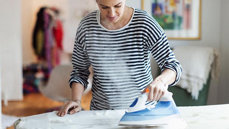 Eine Person bügelt weiße Wäsche mit einem Dampfbügeleisen.