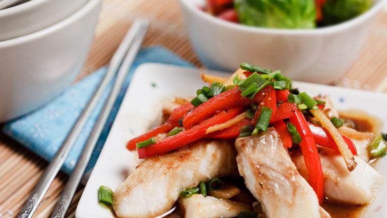 Nahaufnahme eines dampfgegarten Gerichts mit besonders intensiv roten Paprikastreifen.