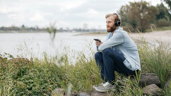 Eine Person sitzt vor einem Fluss auf einem Stein und hört über das Smartphone mit Kopfhörern Musik.