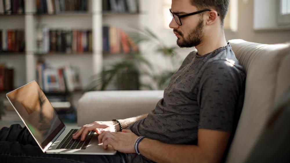 Eine Person sitzt auf dem Sofa und tippt auf einem Laptop herum.