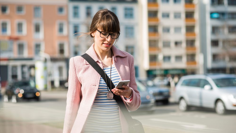 Eine Person geht durch die Stadt und schaut dabei auf ihr Smartphone.