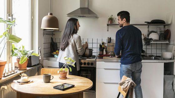 Zwei Personen stehen in einer kleinen Wohnküche und kochen zusammen.