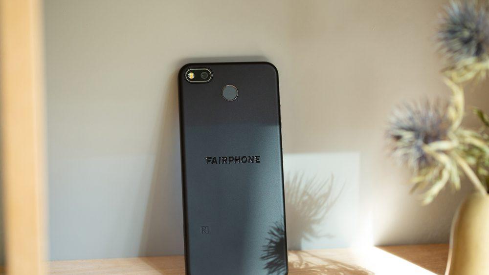 Das Fairphone 3+ lehnt mit dem Display voran an einer Wand.