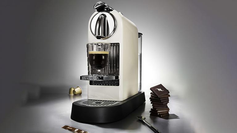 Eine Nespresso CitiZ3 mit ein paar Kapseln und weiterem Zubehör.