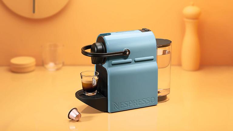 Die Nespresso Inissia auf einem Tisch. Vor der Maschine liegt eine Kapsel.